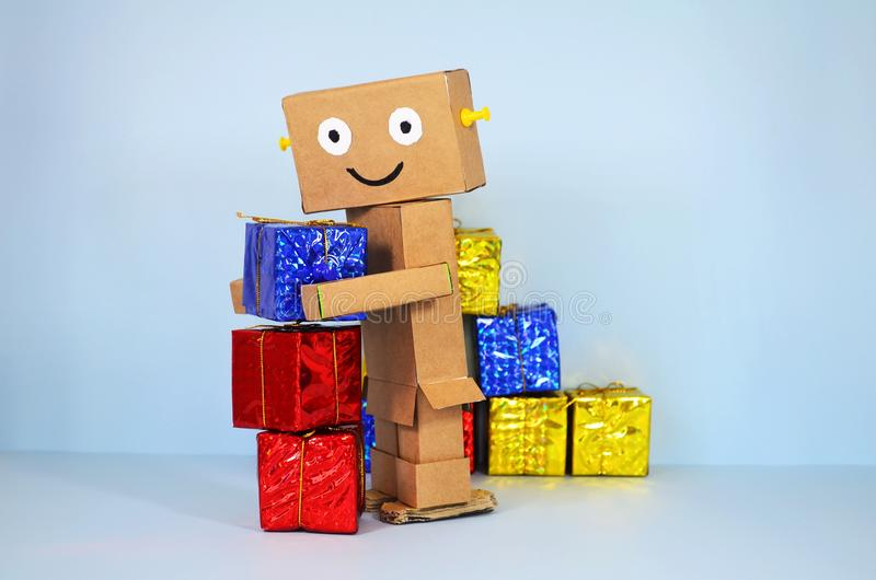 Online shopping, robot brings christmas gifts. Online shopping, funny robot made of cardboard brings chistmas gifts royalty free stock photography