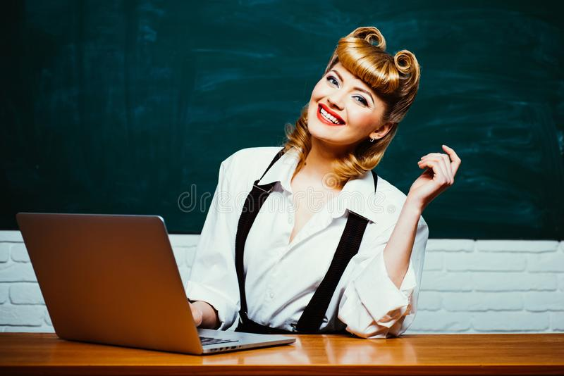 Online shopping for school. Young woman using laptop computer. Female working on laptop. School teacher. Digital stock photos