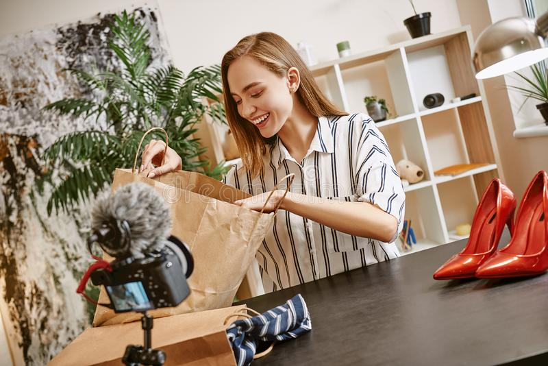 Online shopping. Smiling young blogger showing her new purchases online on a tripod mounted digital camera royalty free stock images