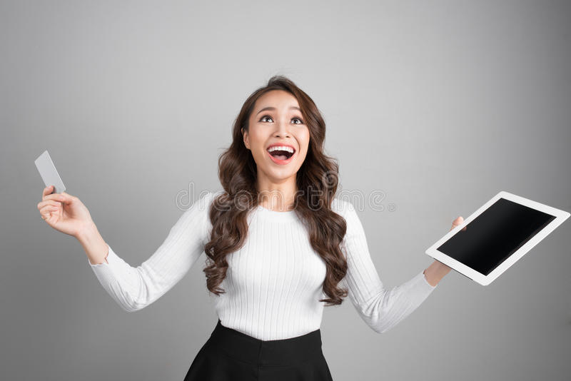 Online shopping, technology and e-money concept. Happy young asian woman with tablet computer and credit card royalty free stock image