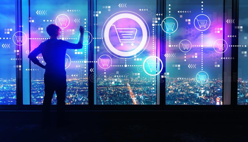 Online shopping theme with man by large windows at night. Online shopping theme with man writing on large windows high above a sprawling city at night stock images