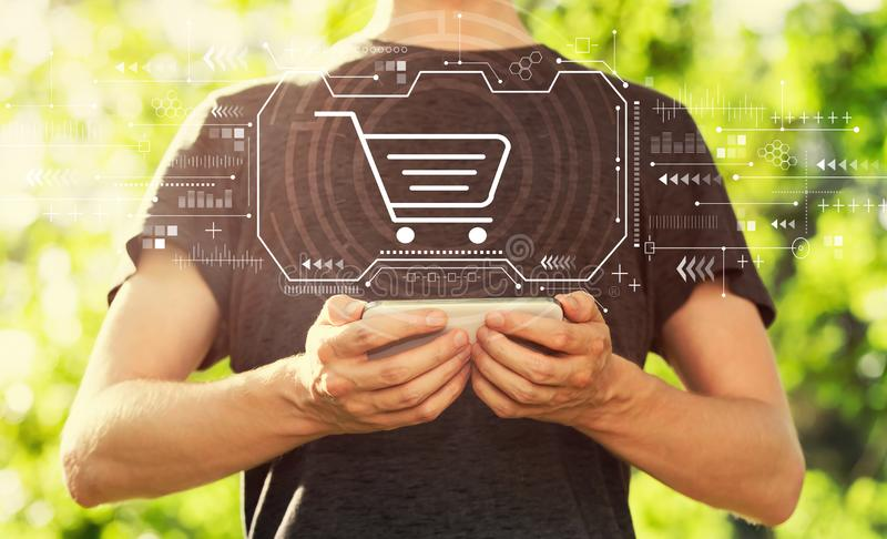 Online shopping theme with man holding his smartphone royalty free stock images
