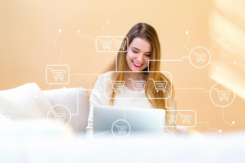 Online shopping theme with young woman using her laptop royalty free stock image