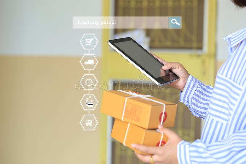 Online shopping, Woman hand holding smart phone and tracking parcel online to update status with hologram, Ecommerce and delivery. Service status tracking royalty free stock images