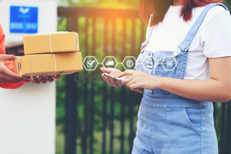 Online shopping, Woman hand holding smartphone and signing receipt of delivery package with delivery man bringing some package at. The home, shipping and postal royalty free stock image