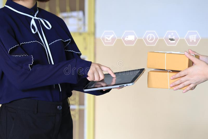 Online shopping, Woman hand holding smartphone and signing receipt of delivery package with delivery man bringing some package at. The home, shipping and postal royalty free stock images