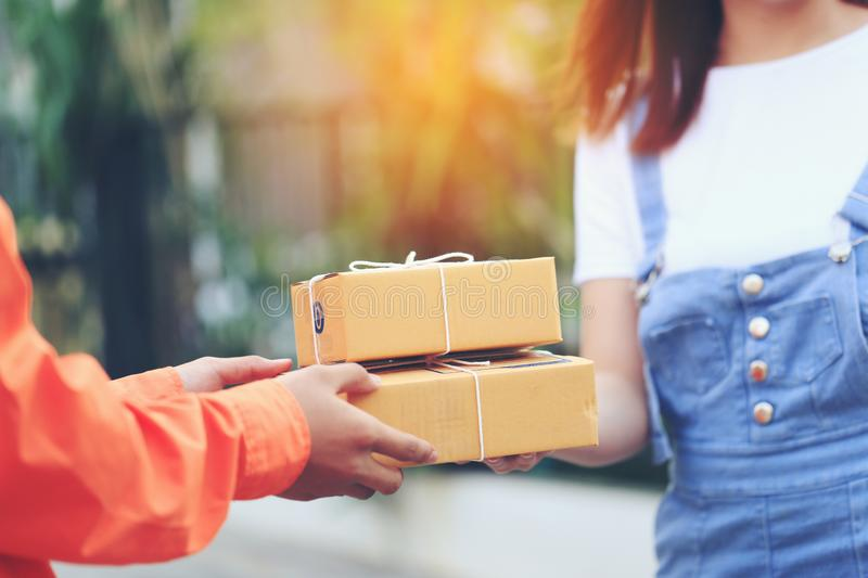 Online shopping, Woman receiving parcel from delivery man bringing some package at the home, shipping and postal service concept.  stock photography