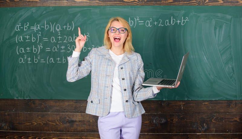 Online-skolgångbegrepp Glasögon för kvinnakläder rymmer bärbara datorn som surfar internet Smart klyftig dam för utbildare med mo royaltyfri foto