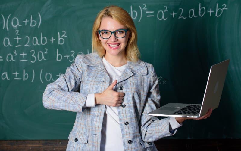 Online-skolg?ngbegrepp Smart klyftig dam f?r utbildare med den moderna b?rbara datorn som s?ker svart tavlabakgrund f?r informati royaltyfri foto
