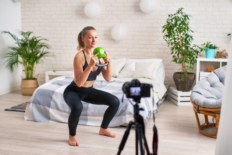 Online-strömlagledaren visar teknik av att utföra övningar med vikter utbildning av benmuskler arkivfoto