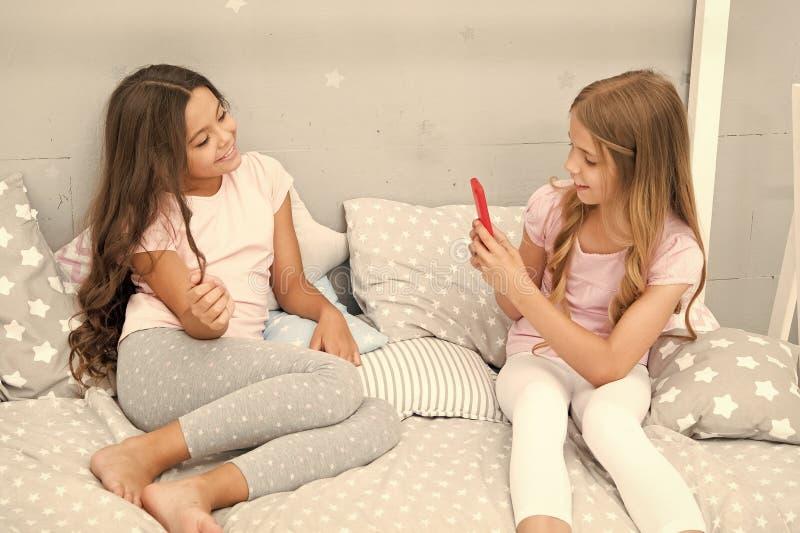 Online-str?mvlogkanal Systrar i pyjamas kopplar av sovrummet och tar det roliga fotoet f?r socialt n?tverkskonto fritid royaltyfria bilder