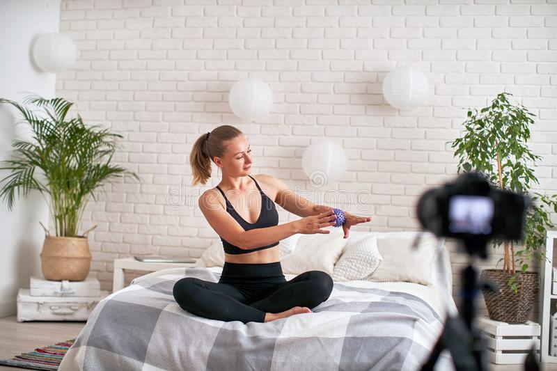 Online stream coach shows technique exercise massage ball. relaxation of the muscles of the hand with a massage ball. in a modern stock image