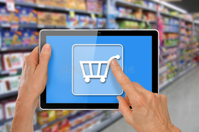 Online Supermarket Shopping Tablet with Hands. Online Supermarket Shopping Hands with computer tablet touching shopping cart icon in front of supermarket