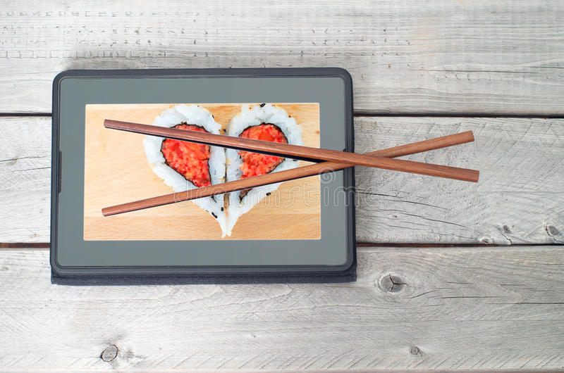 Online sushi food ordering concept. On a wooden table stock photo