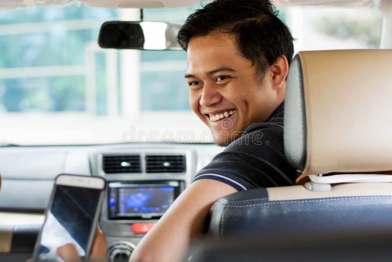 Online-taxichaufför, trans. som reser begrepp - smilling medan skärmen för dräktvisningsmartphone för att betala och att ge sig arkivfoton