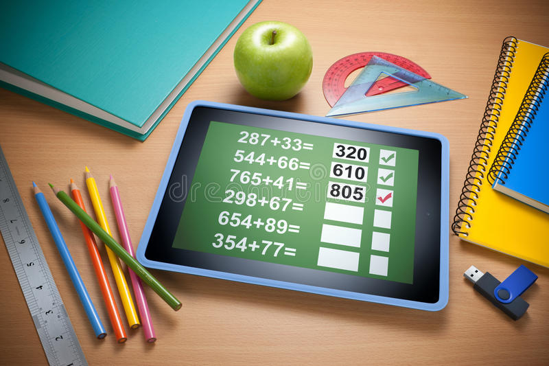 Online Technology Education Learning. An ipad tablet with math problems on the screen. Resting on a school desk with notebooks, colored pencils, apple, usb drive