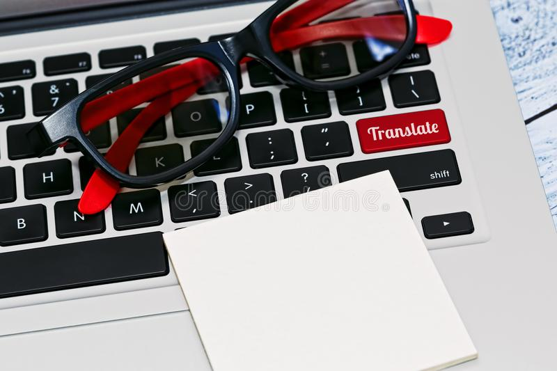 Online translate concept. Laptop PC keyboard with eyeglasses on it with empty checklist and translate key. Online translator concept. Close-up capture. Red color royalty free stock photos