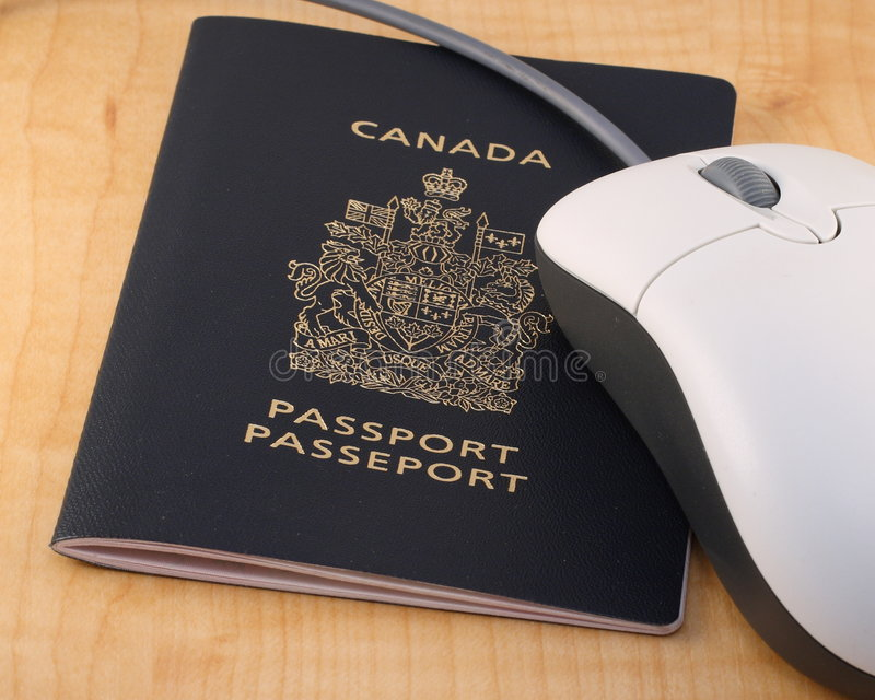 Online travel booking. Concept with a Canadian passport and computer mouse on a desk royalty free stock photography