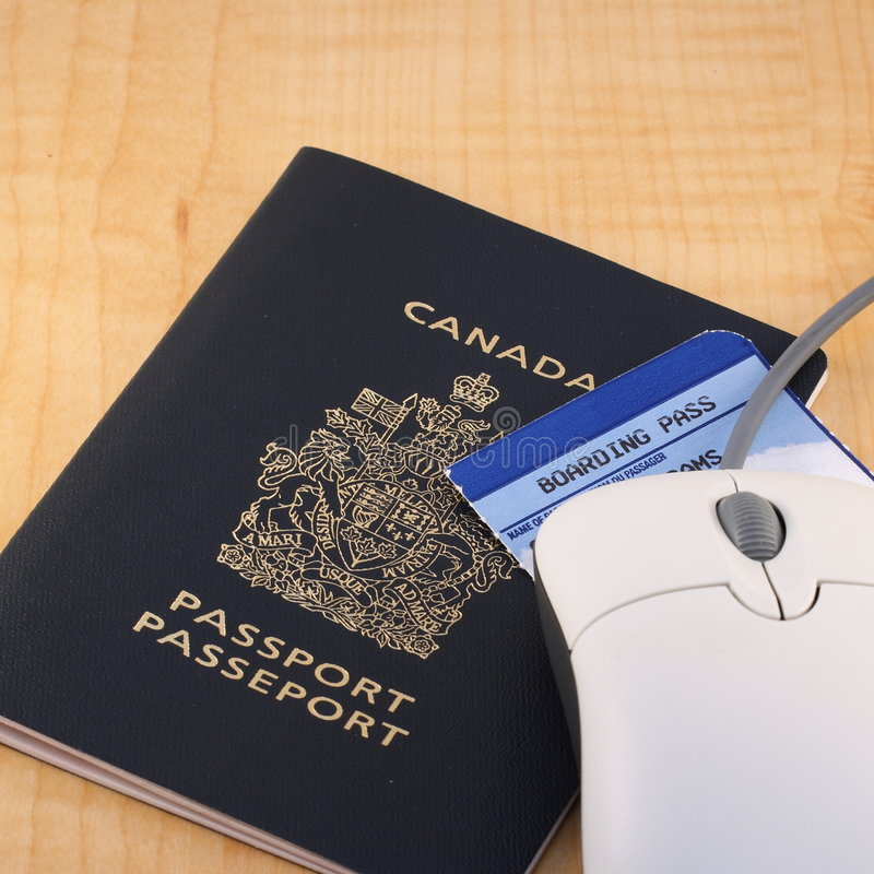 Online travel booking. Concept with a passport, boarding pass and computer mouse on a desk stock photography