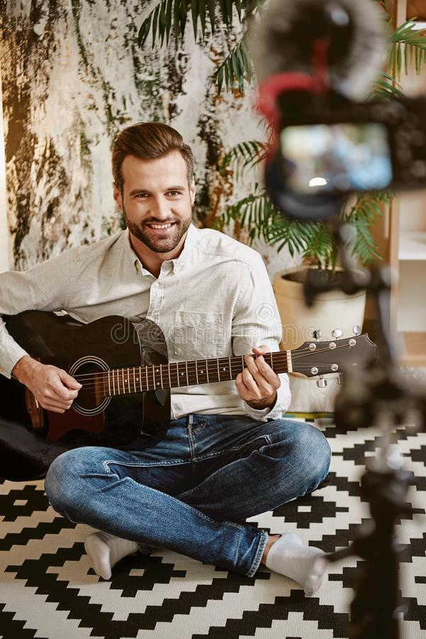 Online tutorial. Young music blogger playing the guitar and smiling, while recording online lesson for his subscribers royalty free stock photos