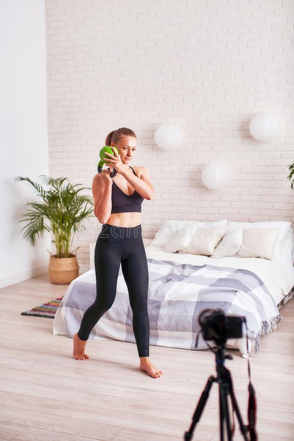 Online-TV-sändninglagledaren visar teknik av att utföra övningar med vikter Utbildning av handmuskler royaltyfria foton