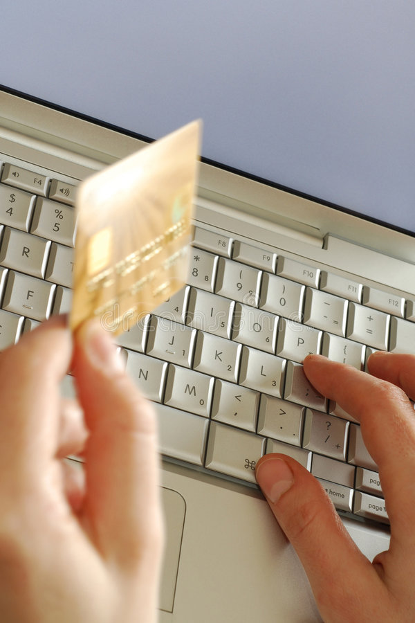 Online vertical. Close up of hands on keyboard holding credit card while shopping online using laptop computer royalty free stock image