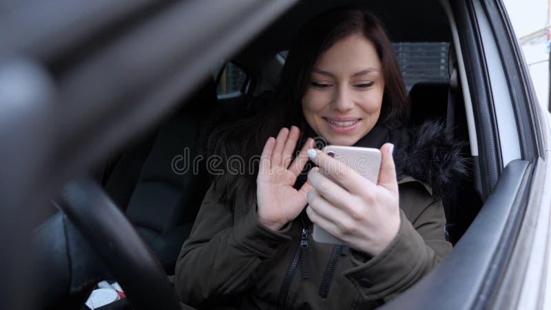 Online-video pratstund av kvinnan, medan sitta i bil royaltyfri foto