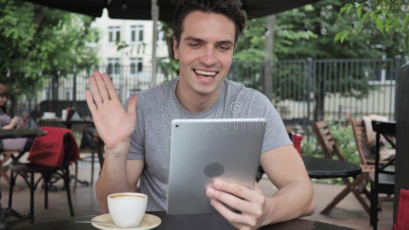 Online-video pratstund på minnestavlan vid mansammanträde i kaféterrass arkivbilder