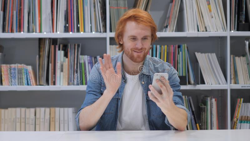 Online-video pratstund på Smartphone kopplar av förbi rödhårig manmannen arkivfoto