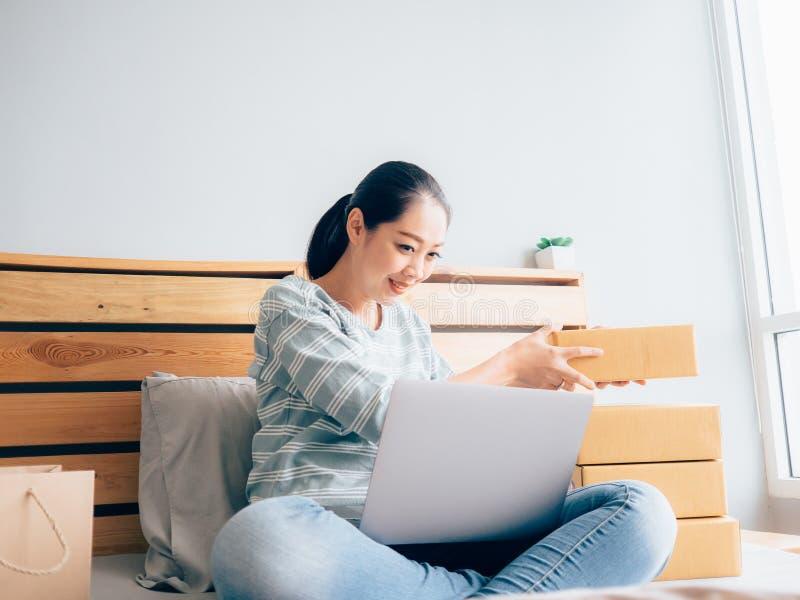 Online w?a?ciciel biznesu kobieta sprawdza jej produktu zapas w sypialni zdjęcia royalty free
