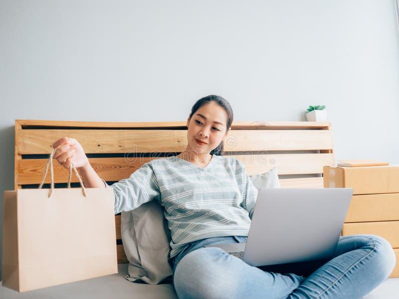 Online w?a?ciciel biznesu kobieta sprawdza jej produktu zapas w sypialni obraz stock