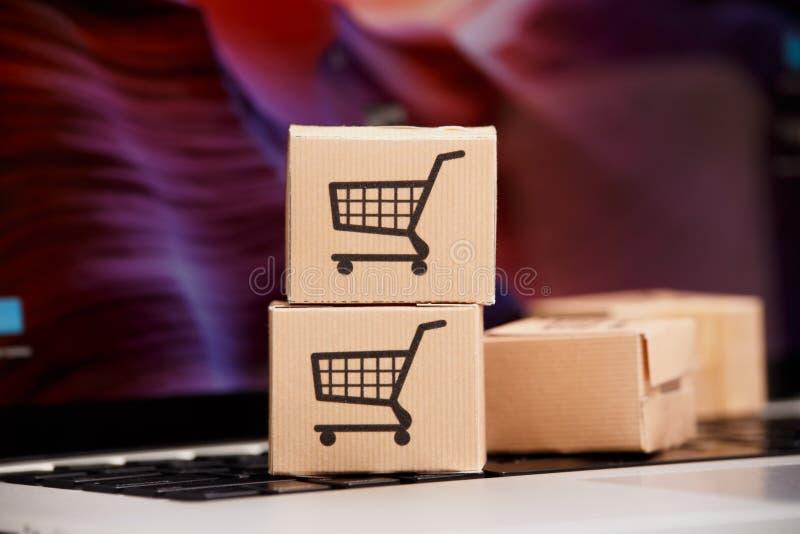 Online Winkelend elektronische handel en van de leveringsdienst concept: Document kartons met een kar of karretjeembleem op lapto stock foto's