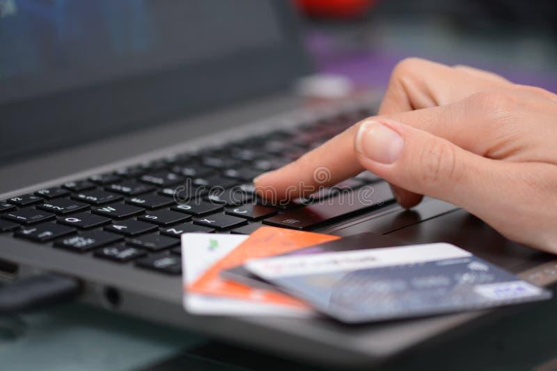 Online winkelend en Internet-bankwezenconcepten door een vrouw worden voorgesteld die technologie en creditcards gebruiken die royalty-vrije stock afbeeldingen