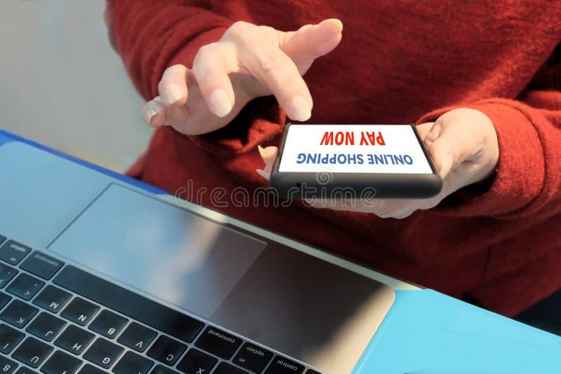 Online winkelend, koop nu Close-up van vrouwelijke handen met een mobiele telefoon op de achtergrond van laptop Concept stock foto's