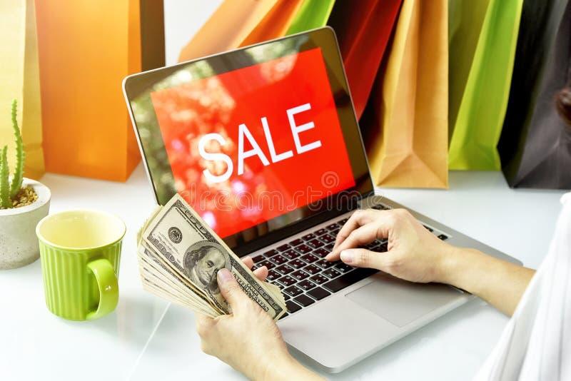 Online winkelend, Shopaholic-het geldcontant geld van de vrouwenholding, het teken van de Verkoopbevordering op laptop computer stock fotografie
