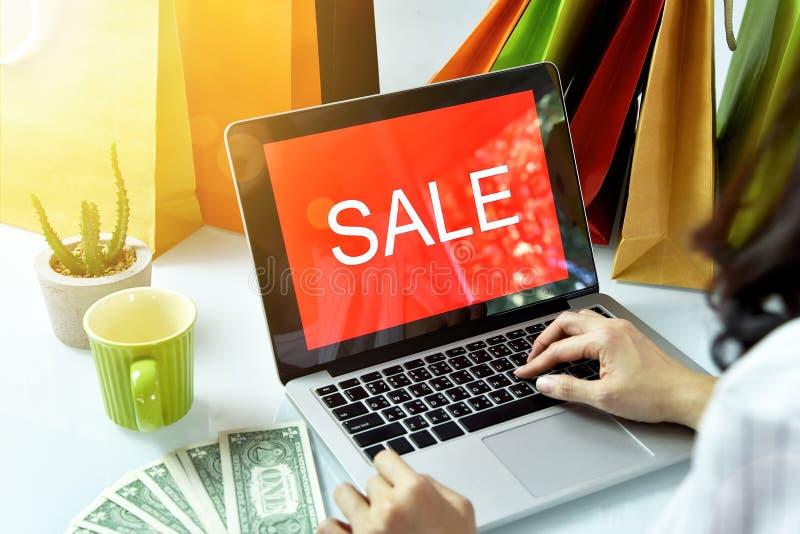 Online winkelend, Shopaholic-vrouw met het teken van de verkoopbevordering op laptop computer royalty-vrije stock foto