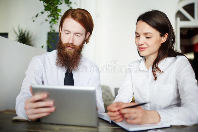Online working. Confident managers looking at touchscreen and discussing data stock images
