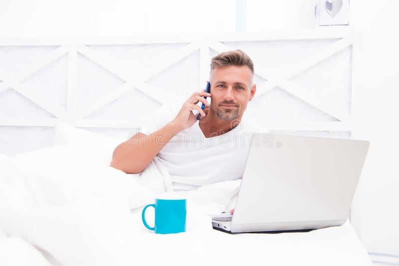 Online world. Man surfing internet work online. Already at work. Digital marketing. Remote access. Hipster bearded guy. Pajamas freelance worker relaxing at royalty free stock photo