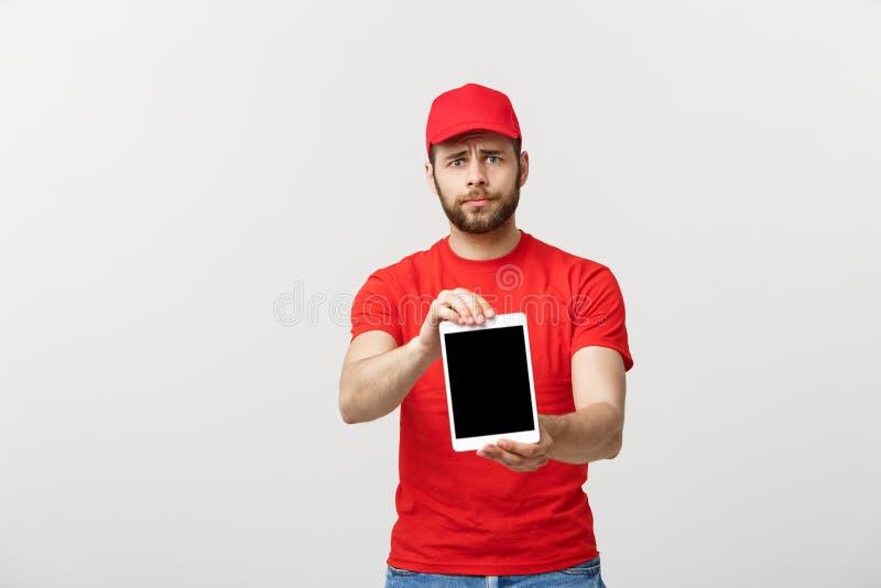 Online zakupy, dostawy, technologii i stylu życia pojęcie, - uśmiechnięty doręczeniowy mężczyzna przedstawia pastylkę w jego ręka zdjęcia royalty free