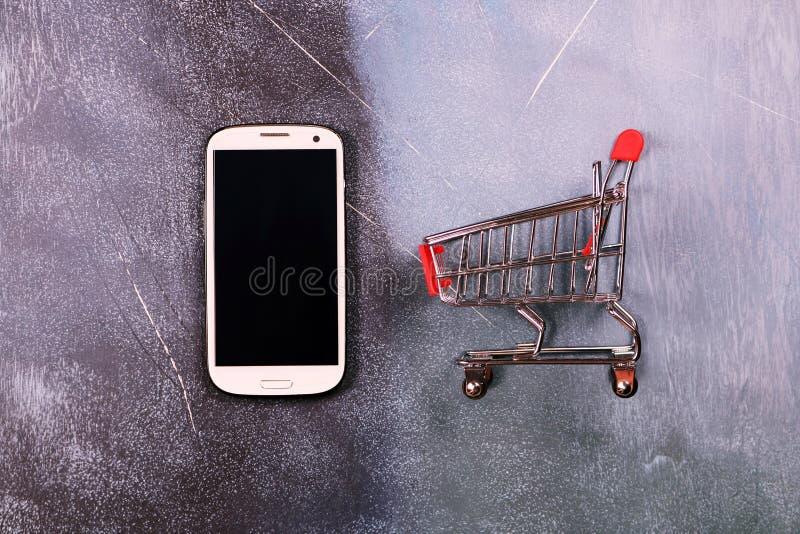 Online zakupy pojęcie, wózek na zakupy i mądrze telefon na textured tle, fotografia royalty free