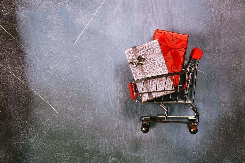Online zakupy pojęcie, wózek na zakupy i prezentów pudełka na textured tle, zdjęcia royalty free