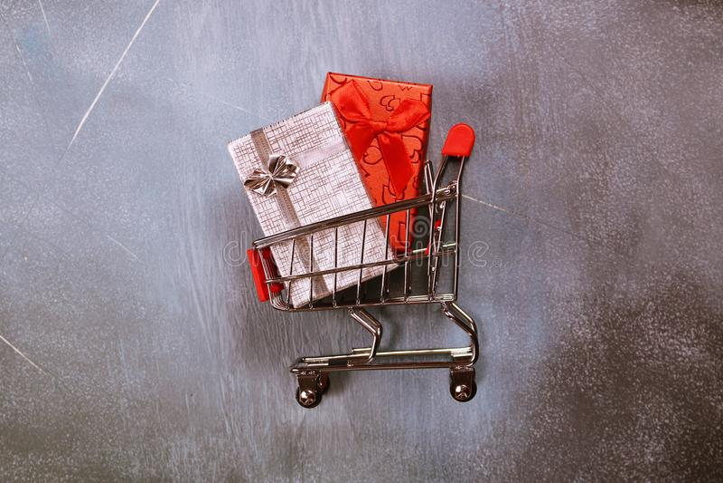 Online zakupy pojęcie, wózek na zakupy i prezentów pudełka na textured tle, obraz royalty free