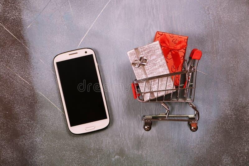 Online zakupy pojęcie, wózek na zakupy i prezentów pudełka na textured tle, zdjęcia stock