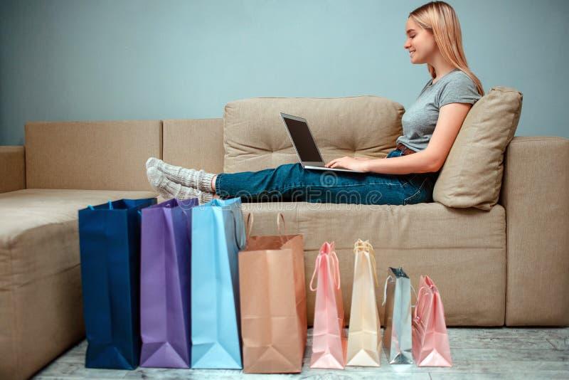 Online zakupy w domu Młoda uśmiechnięta kobieta siedzi na kanapie i używa laptop blisko kolorowych toreb na zakupy obrazy royalty free