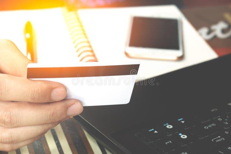 Online zapłata, man& x27; s wręcza trzymać kredytową kartę nad laptopem fotografia royalty free
