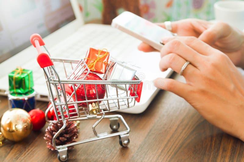 Online zapłata, Zamyka up przy prezentów pudełkami w wózek na zakupy i boże narodzenie dekoracja, kobieta wręcza używać smartphon zdjęcie stock
