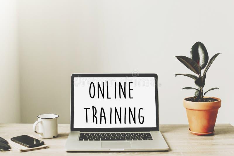 Onlinego szkolenia tekst na laptopu ekranie na drewnianym desktop z pho obrazy royalty free