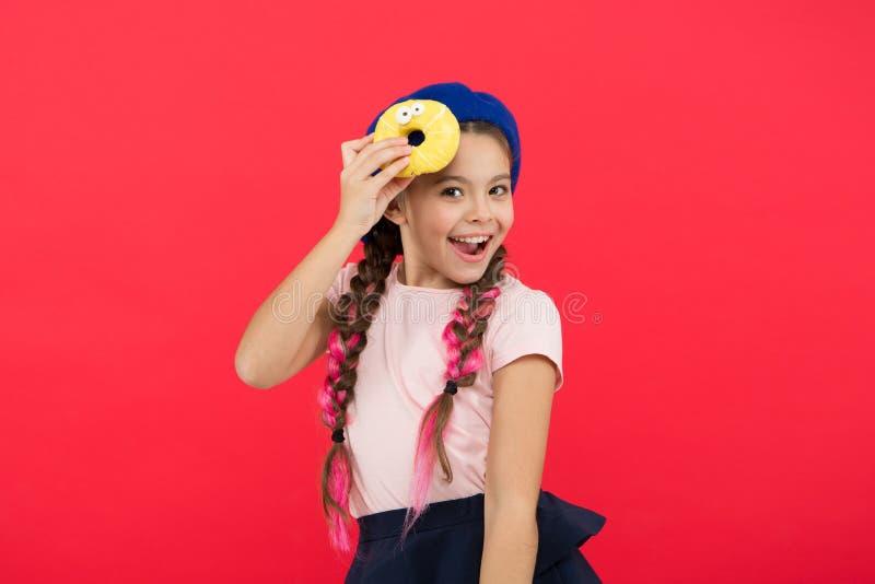 Onmogelijk om zich tegen verse gemaakte doughnut te verzetten De meisjesgreep verglaasde leuke doughnut in hand rode achtergrond  stock fotografie