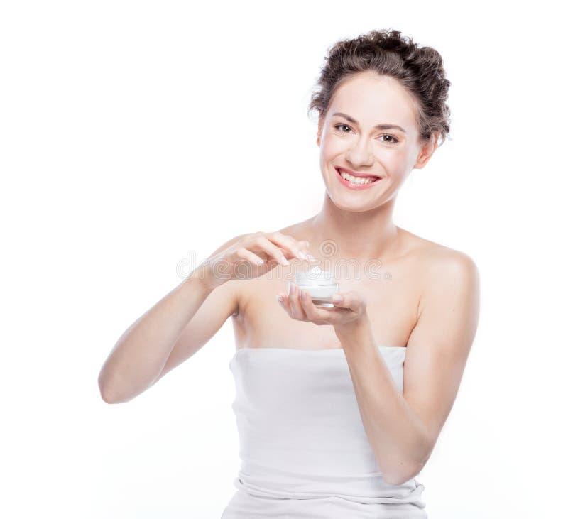 Ono uśmiecha się, atrakcyjna kobieta używa moisturizer fotografia stock