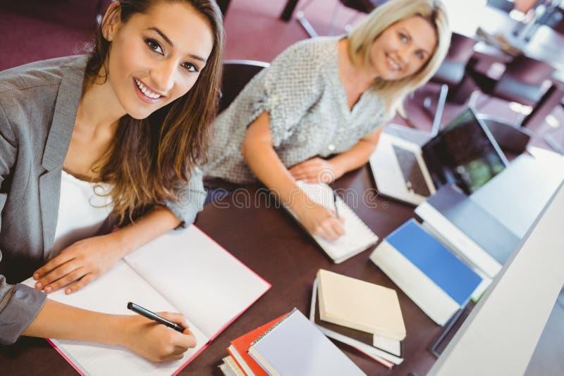 Ono uśmiecha się dorośleć kobieta uczni pisze notatkach przy biurkiem fotografia stock